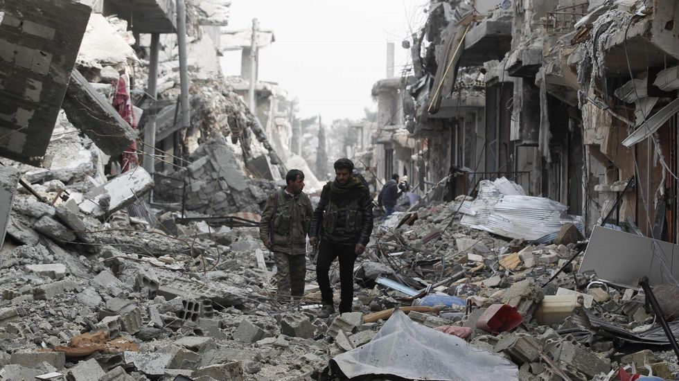 Fighters of the Kurdish People's Protection Units (YPG) walk past damaged buildings in Kobanî